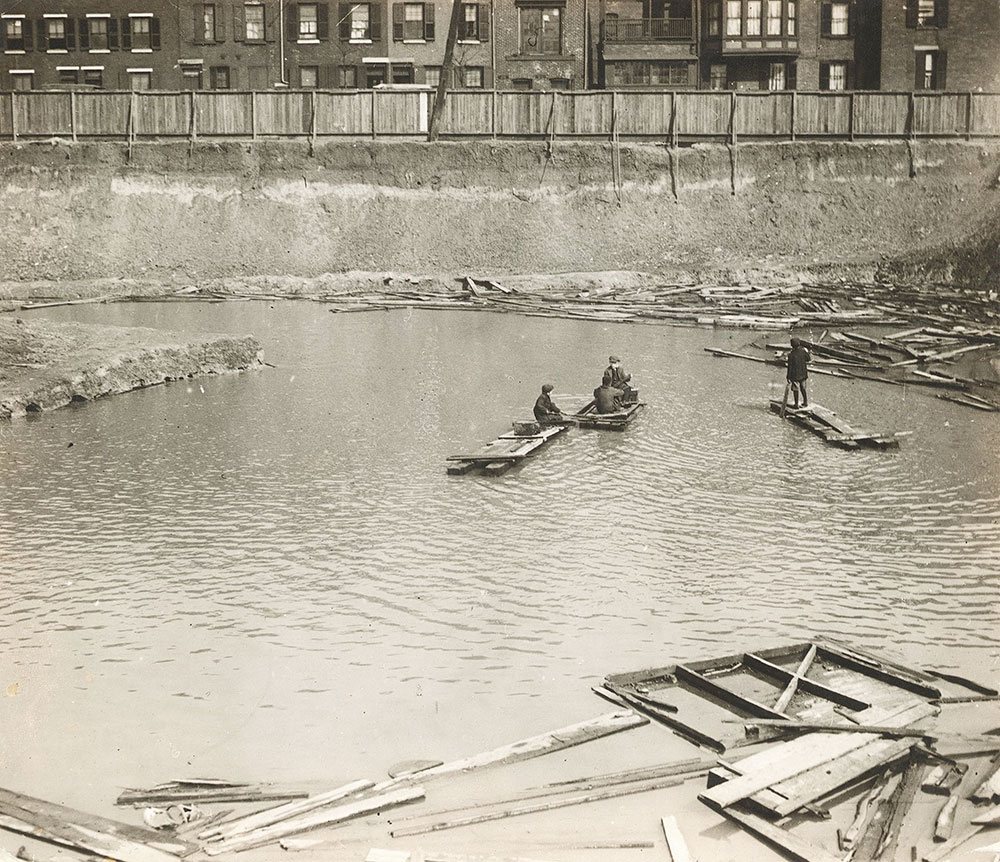 Boys rafting in the water-filled hole excavated for the foundations of the Central Library of the Free Library of Philadelphia, c. 1919