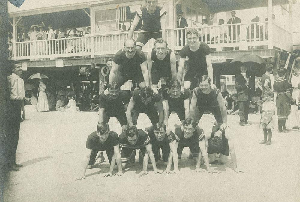 Men in Pyramid Pose on Beach