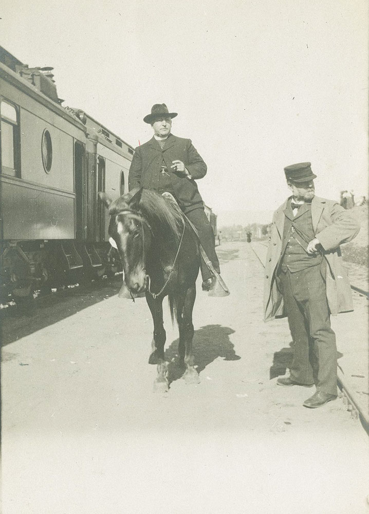 Large man on horse next to train