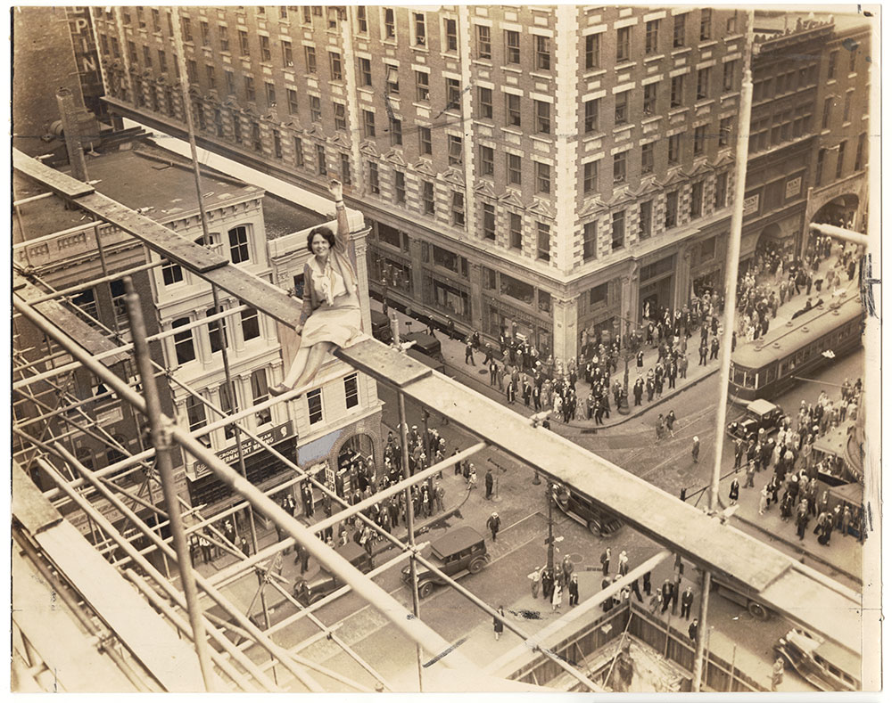 Vivian Shirley sitting on scaffolding atop the Federal Reserve Bank (under construction)